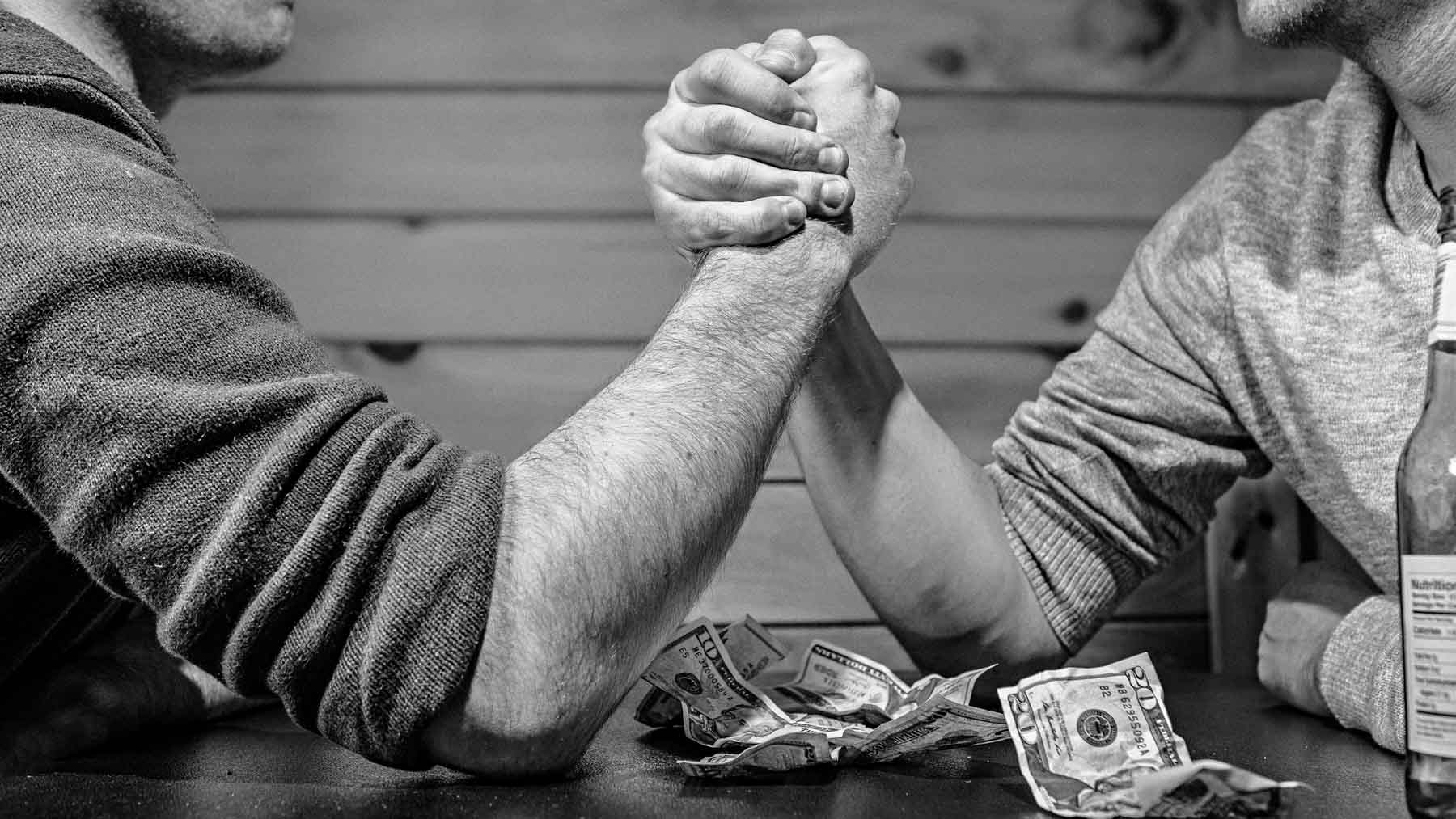 two men arm wrestling with elbows on wooden table and money lying between them