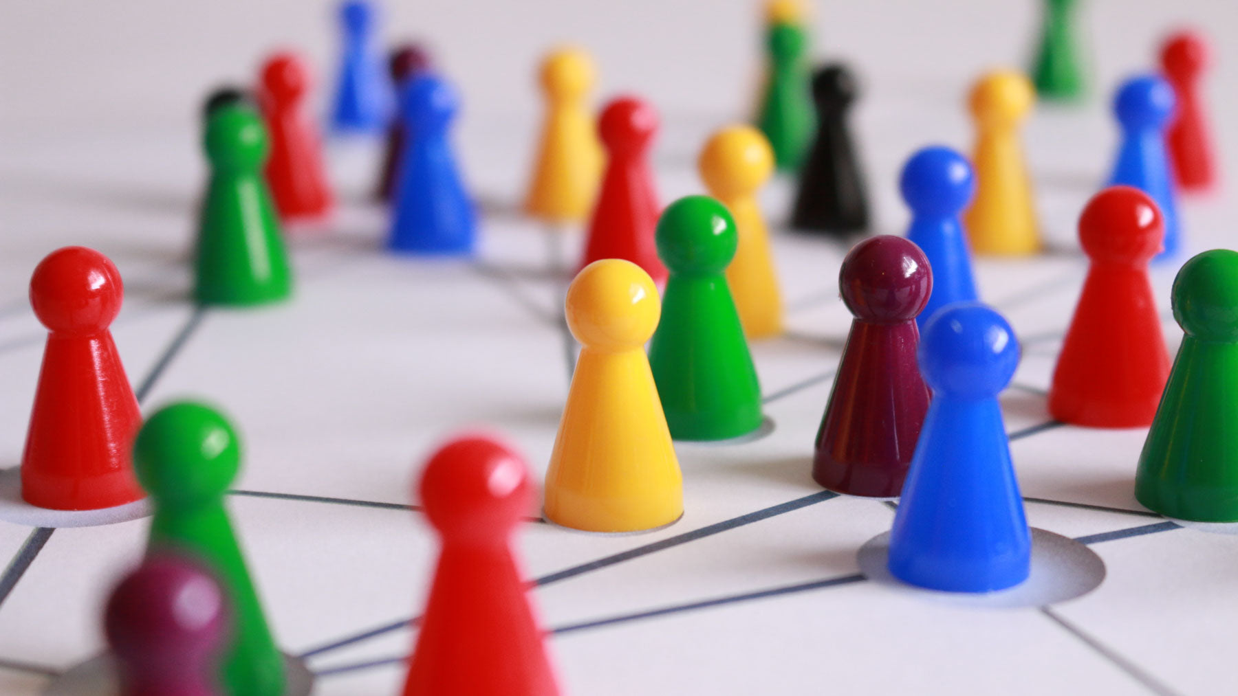 coloured plastic people-shaped counters grouped together to symbolise community
