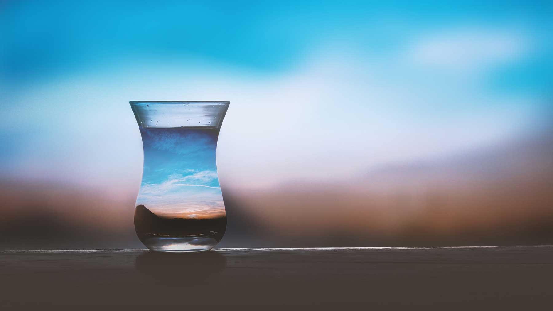A glass jug of water in front of pink and blue sunset sky to represent going sober