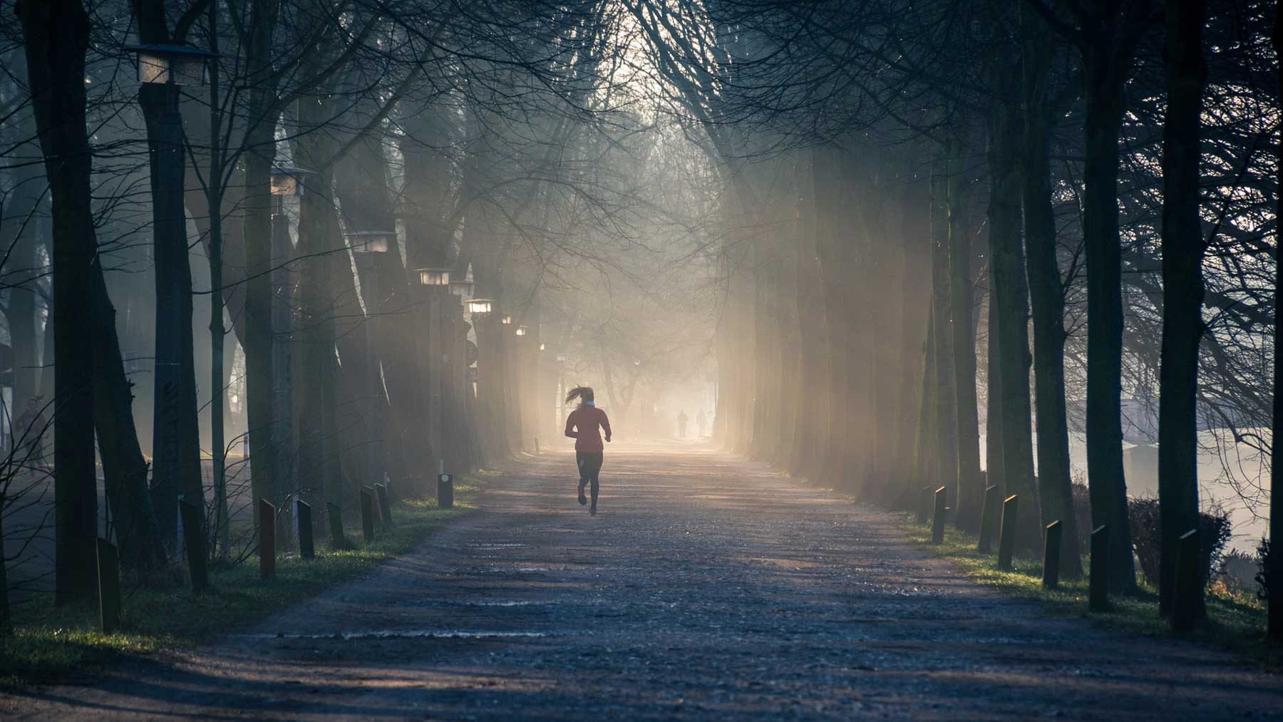 woman running through avenue of trees with sunlight filtering through
