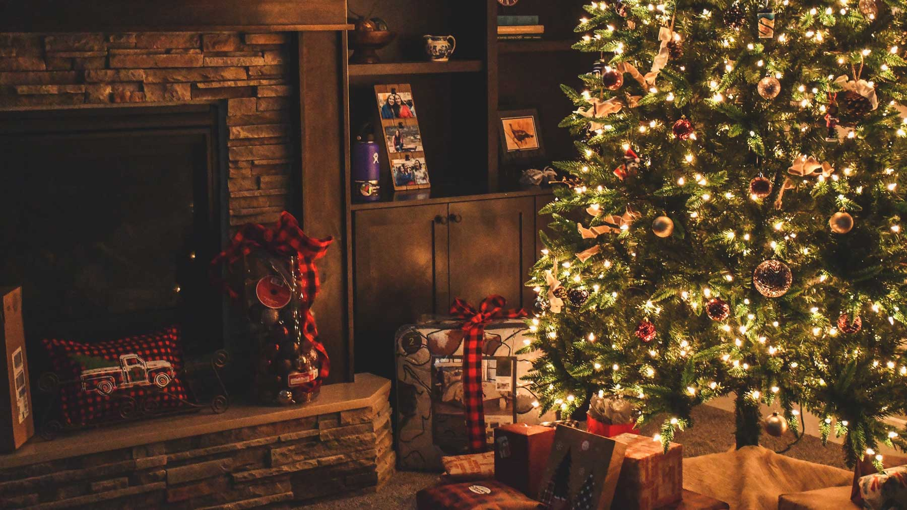 Christmas tree with presents underneath next to fireplace with decorations