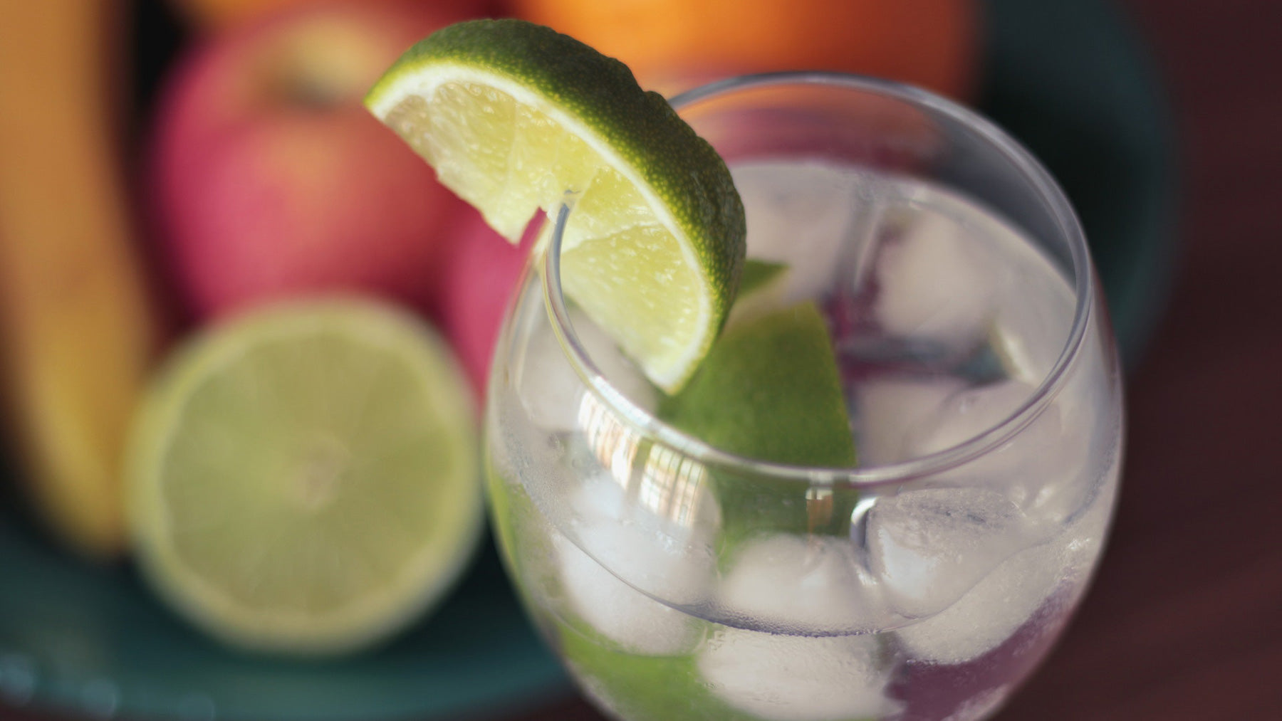 aerial view of glass of water with ice and slice of lime and fruit on table in background