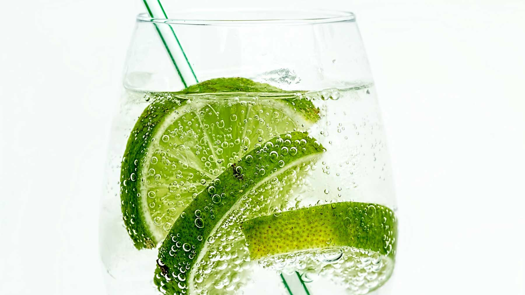 clear glass with soda water and lime slices with straw