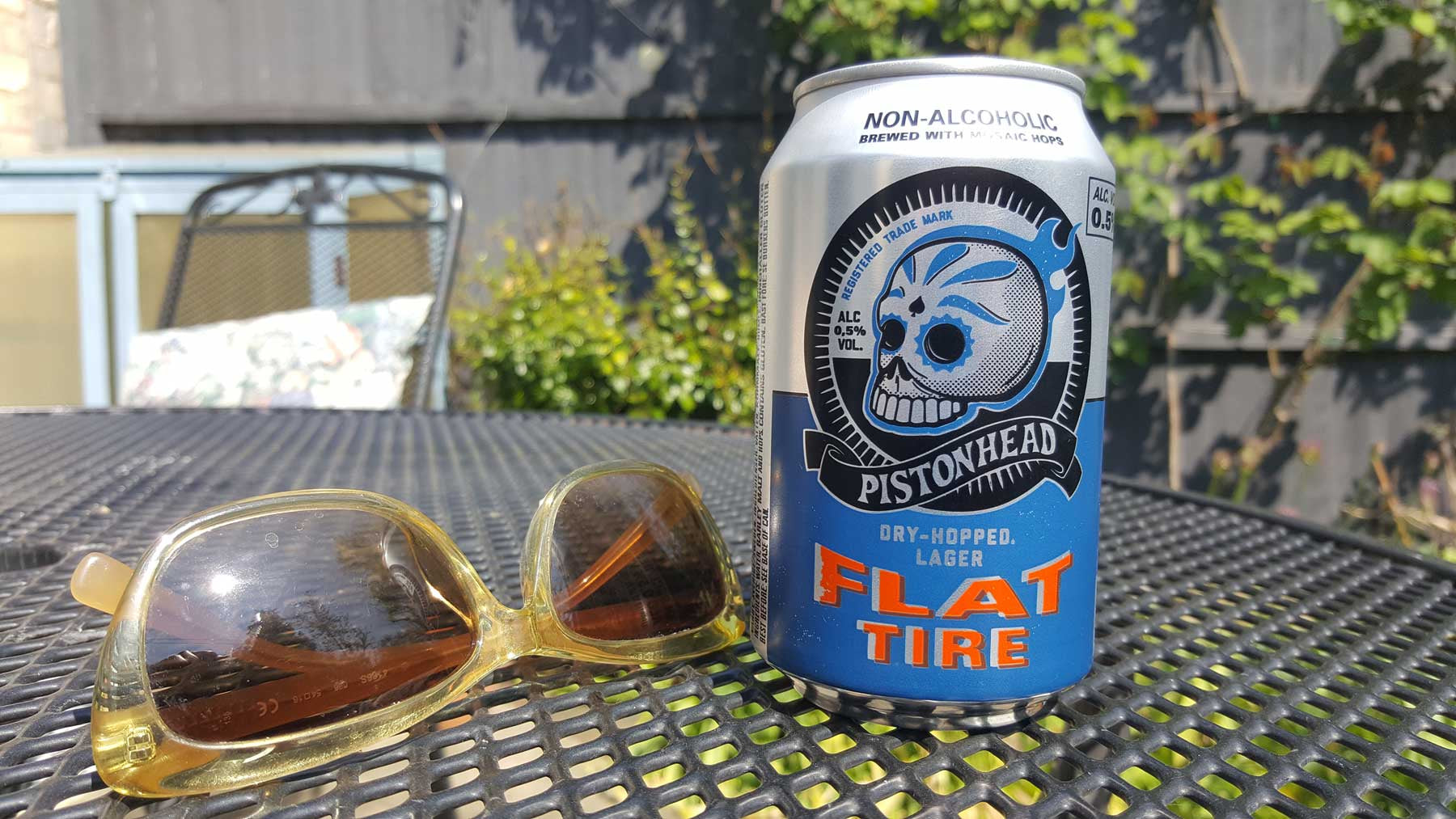 "a can of ""Piston Head"" non-alcoholic lager on a garden table in the sun"