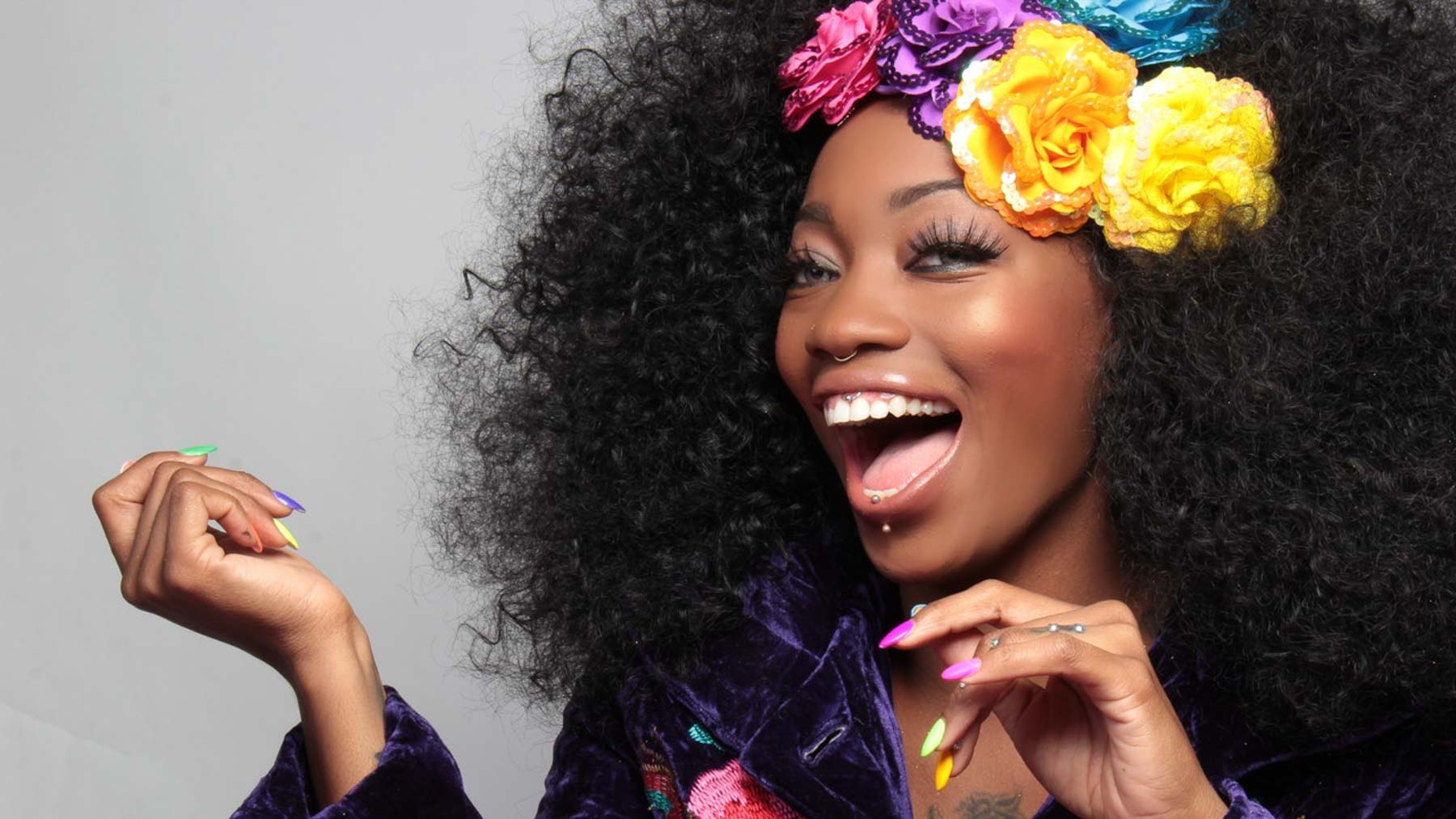 woman smiling confidently at the camera with bright flowers in her hair to represent sober confidence