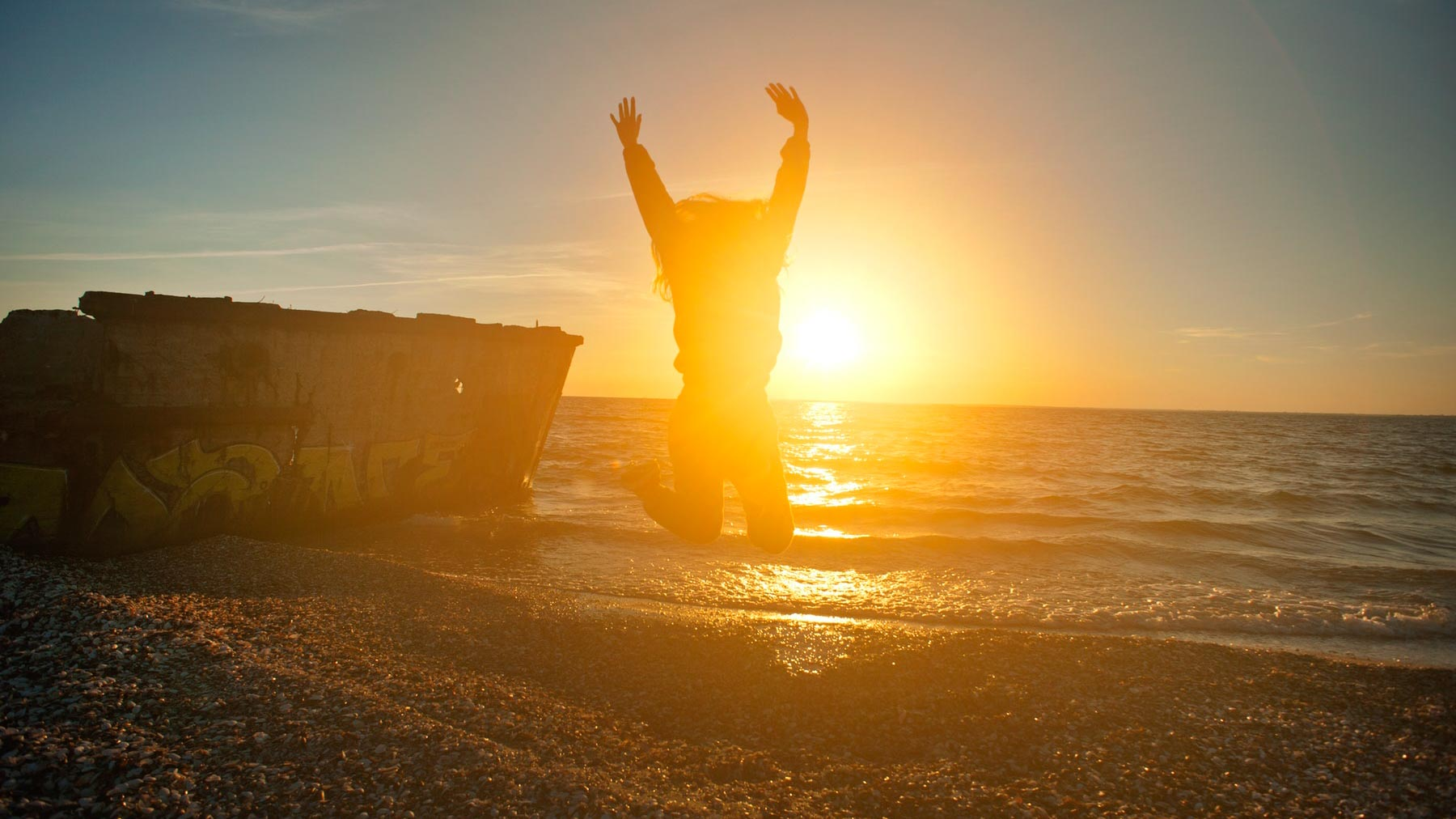 person jumping joyfully on beach in sunset to represent relief and joy