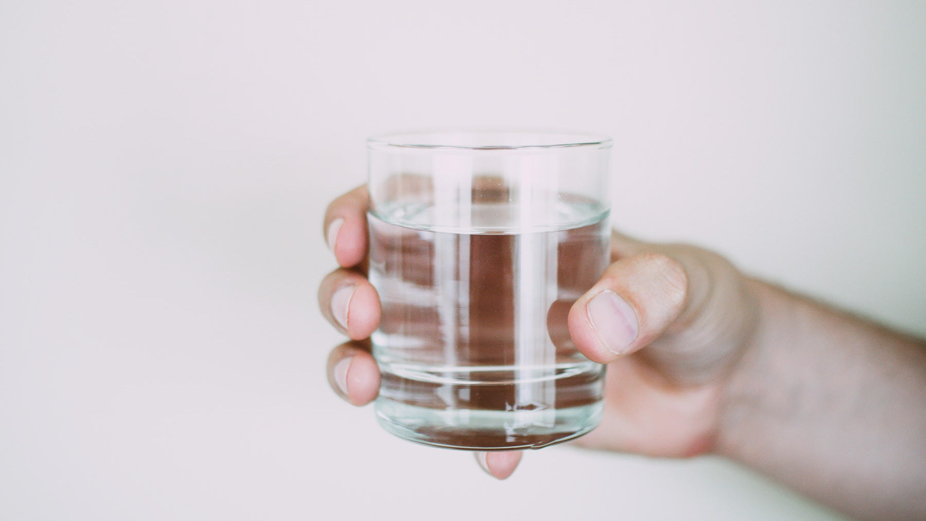 a hand holding a small clear glass of water to represent a healthy sober lifestyle