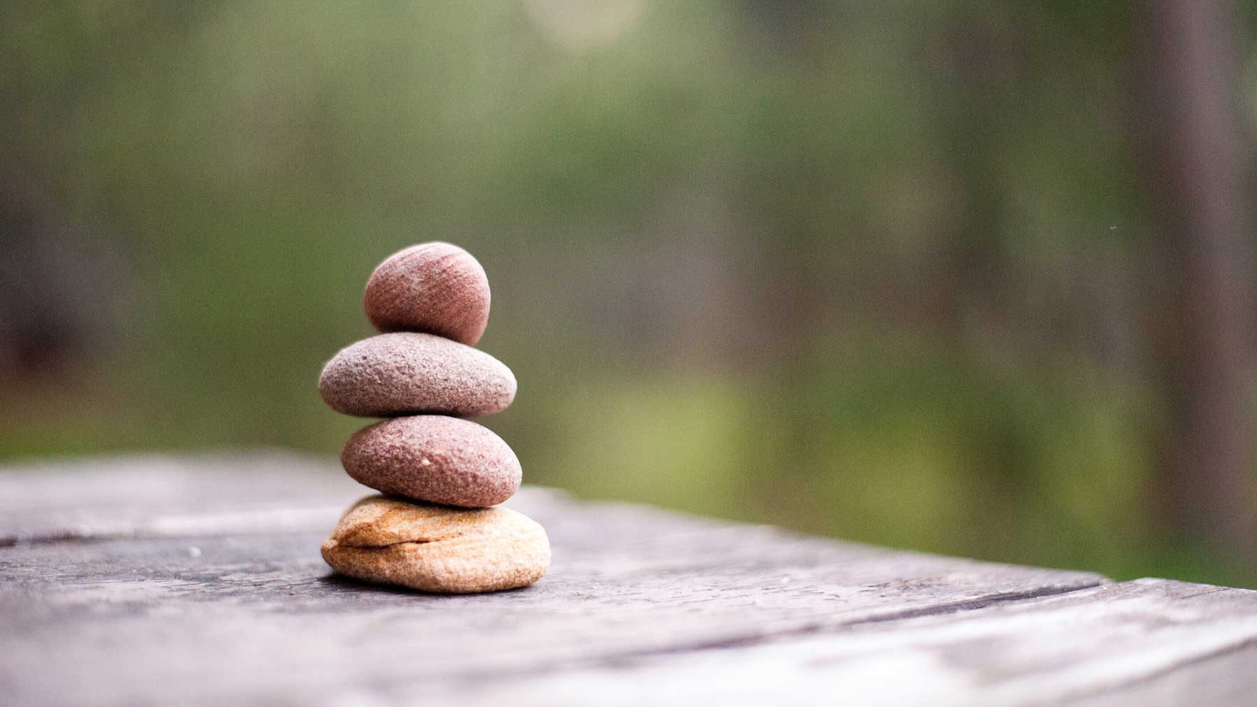 pile of smooth stones balancing on top of each other to represent a balanced approach