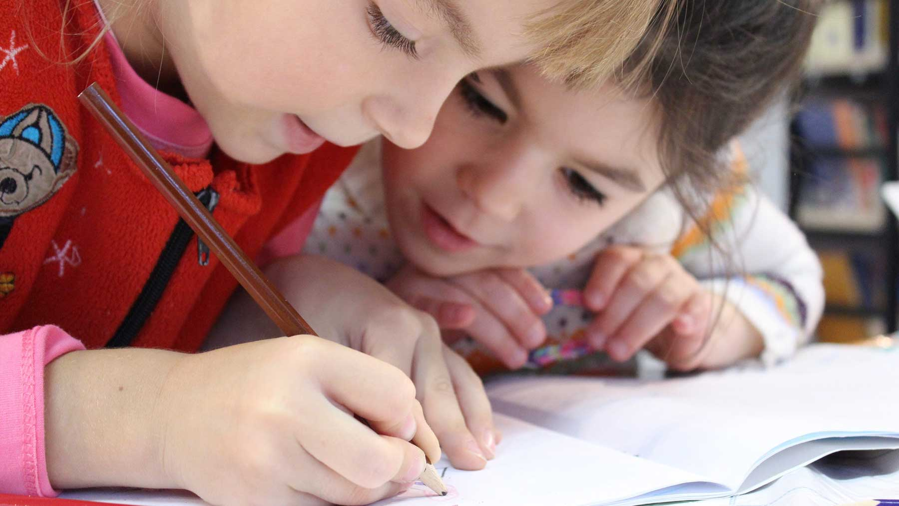two young children learning to write with heads bent over notebooks and pencils