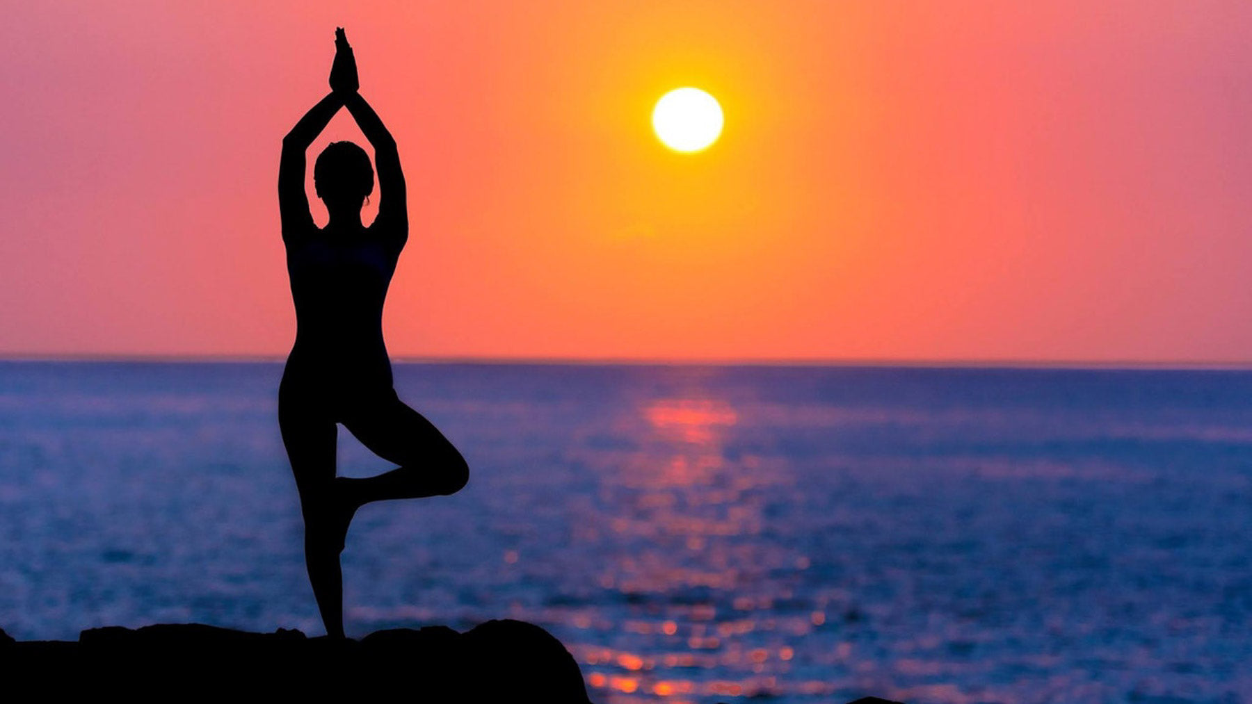 silhouette of woman in yoga pose in front of beautiful sunset to represent sober wellbeing