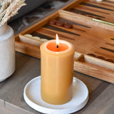 a bees wax pillar candle burning on a coffee table with a board game