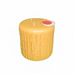 Round, large three wick beeswax candle, golden yellow in color that has the appearance of wax dripping down the side.