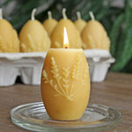 Beeswax egg candle, burning, with egg carton of candles in background