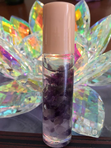 Clear glass roller vial with natural gemstones chips and lavender essential oil.