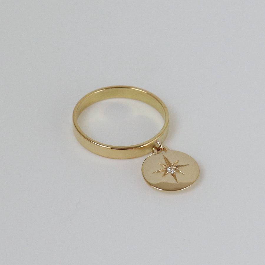 Izaskun Zabala jewelry dangle medallion ring with a sapphire set on an engraved star