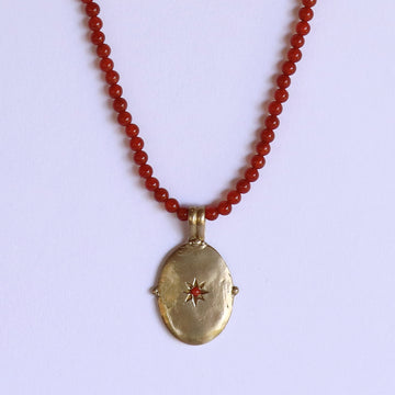 Izaskun Zabala jewelry oval medallion with star set coral cabochon pendant, and carnelian beads necklace