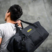 Load image into Gallery viewer, man carrying a black sport duffel which has a yellow metallic label