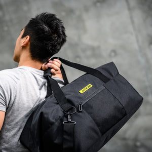 man carrying a black sport duffel which has a yellow metallic label