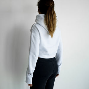 back of a woman in white cropped hoodie