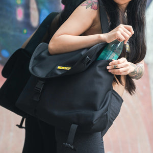 woman putting a water bottle in a black crossbody bag