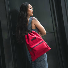Load image into Gallery viewer, woman in a knit jumpsuit carrying a red drawstring bag