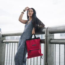 Load image into Gallery viewer, woman in a knit jumpsuit carrying red two-way drawstring bag