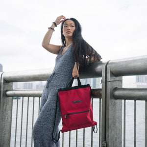 woman in a knit jumpsuit carrying red two-way drawstring bag