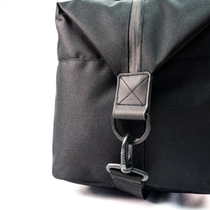 shoulder strap attached to a d-loop of black duffel bag