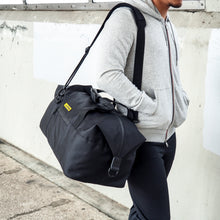 Load image into Gallery viewer, man carrying a black duffel with his hands inside hoodie's pockets