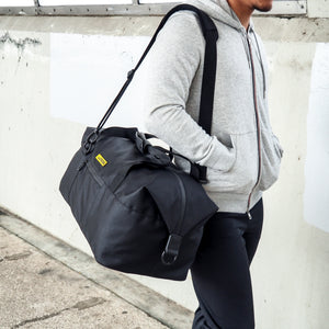 man carrying a black duffel with his hands inside hoodie's pockets