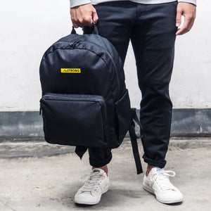 holding a black backpack's top handle