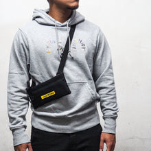 Load image into Gallery viewer,  man in grey hoodie carrying a small crossbody bag