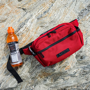 red belt bag and energy drink on a rock