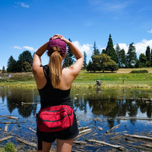 Load image into Gallery viewer, woman with a red belt bag in front of a mirror lake