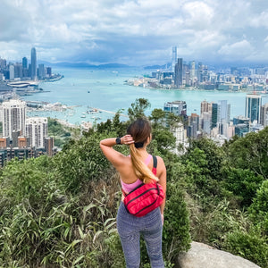 woman carrying a red belt bag with the view of Victoria harbour
