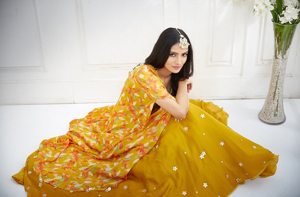 GOLD BLOUSE WITH MUSTARD PRINTED CAPE AND EMBROIDERED LEHENGA