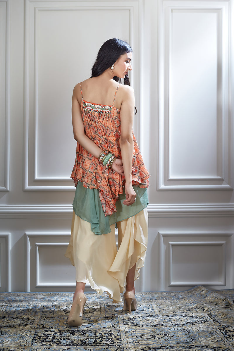 A printed chiffon asymmetrical layer top paired with an ivory layered sharara.
