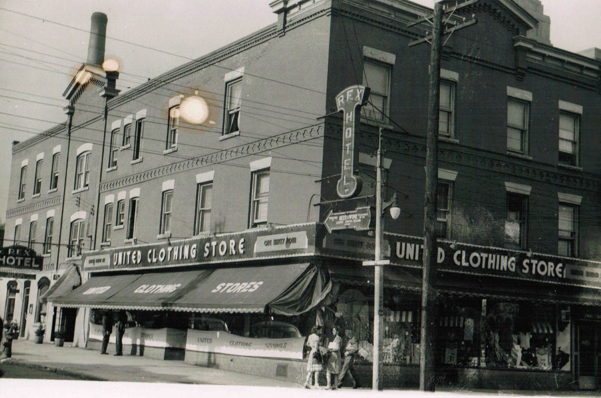 A picture of The Rex building in the 1950's, when it changed from being just clothing store to offering a beverage room and monthly accommodations.