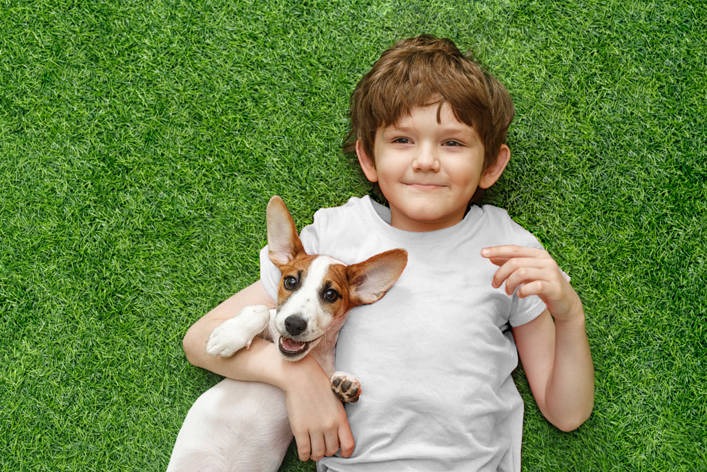Boy lays with healthy puppy