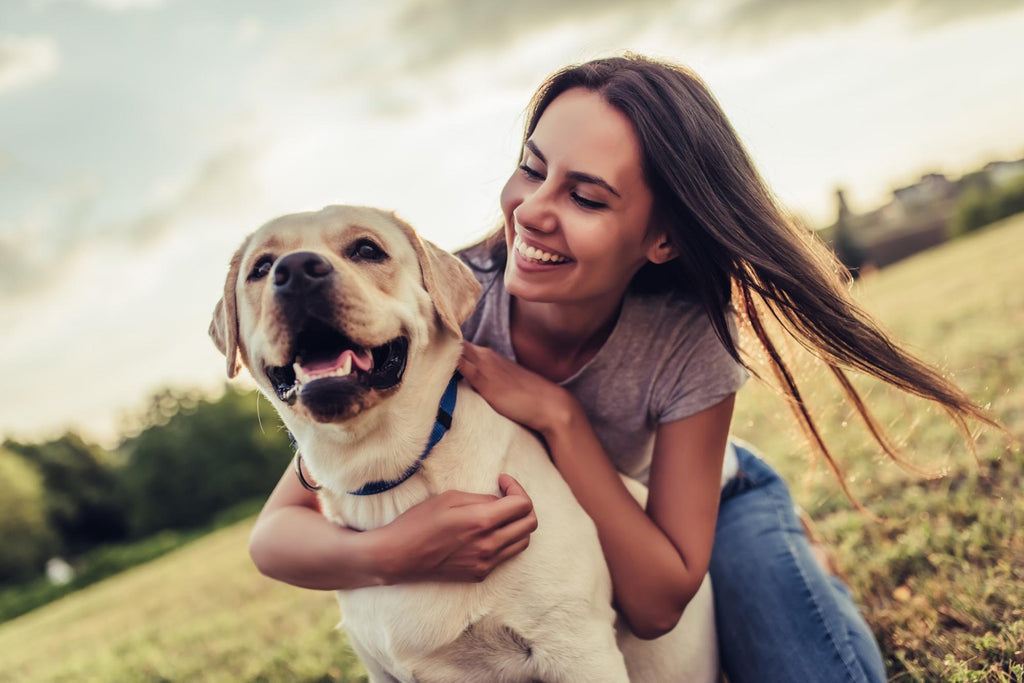 Fish oil for dogs: Girl hugging the dog