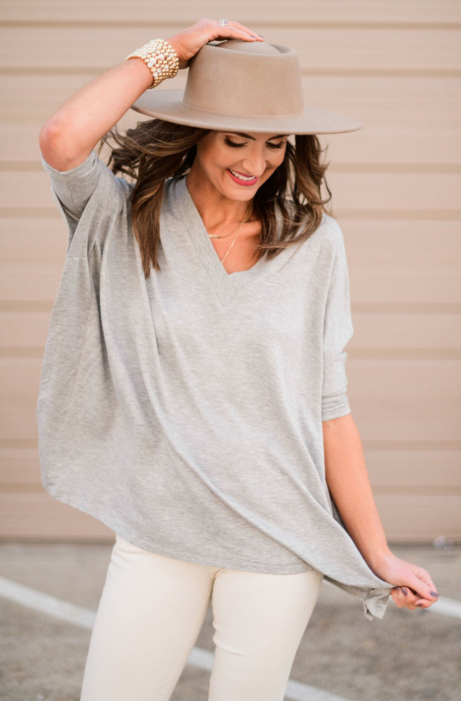 heathery grey v neck poncho w/ fitted sleeves, beige distressed skinnies, khaki wool hat, gold bracelets, evil eye necklace, fresh start, January collection, spring outfits, shop style your senses by Mallory Fitzsimmons
