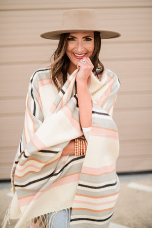 pastel stripe poncho w/ fringe, medium washed distressed mom jeans, off white hacci knit oversized top, khaki wool hat, gold bracelets, booties, fresh start, January collection, spring outfits, shop style your senses by Mallory Fitzsimmons