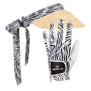 Women's golf visor with straw brim, black and white Zebra print band that ties into a bow at the back with matching women's golf glove in black and white Zebra print and white leather palm