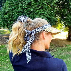Female golfer wearing women's golf visor with straw brim with black and white Zebra print band that ties into a bow at the back. Golfer is wearing her hair in pony and clutching it with matching women's golf glove in black and white Zebra print with white leather palm.