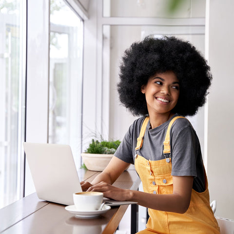 black girl natural hair laptop in front of window with coffee