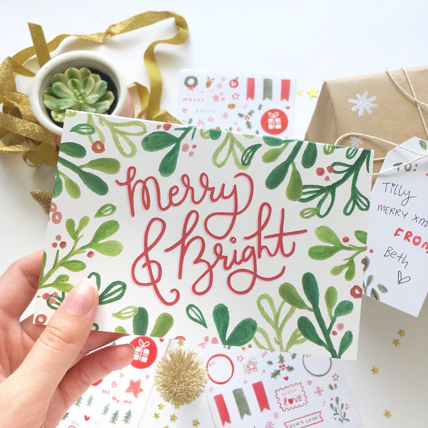 "Christmas card decorated with green mistletoe illustrations and the message ""Merry & Bright"" in red hand writing."