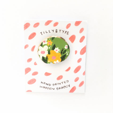 Light green wooden brooch painted with floral designs in shades of white, yellow, pink and dark green
