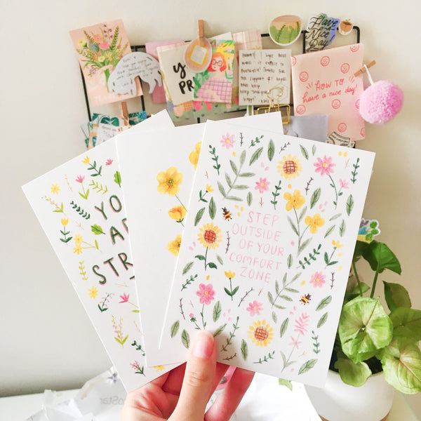 "A hand holds up a set of colourful postcards in front of a desk with plants. The front postcard is decorated with pink, yellow and green floral illustrations, and reads in the middle ""STEP OUTSIDE OF YOUR COMFORT ZONE""."