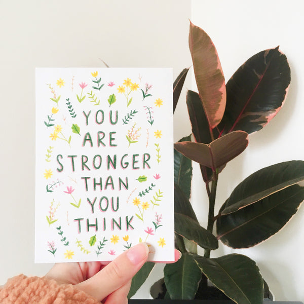 "Hand holding an illustrated postcard in front of a plant. The postcard is decorated with illustrations of small green, yellow and pink plants, and in the middle is the handwritten quote ""YOU ARE STRONGER THAN YOU THINK""."