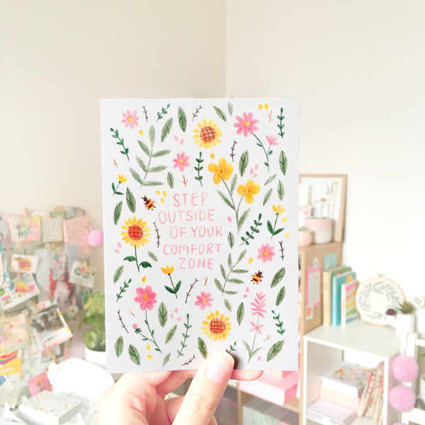 "A hand holds up an illustrated postcard in a colourful office. The postcard is decorated with pink, yellow and green floral illustrations, and reads in the middle ""STEP OUTSIDE OF YOUR COMFORT ZONE""."